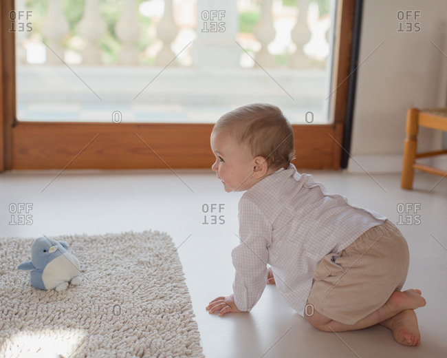 Side view of adorable little kid in casual clothes crawling on floor at home and curiously looking away