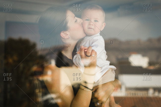 Content woman in casual outfit embracing and kissing cute toddler while standing near window at home