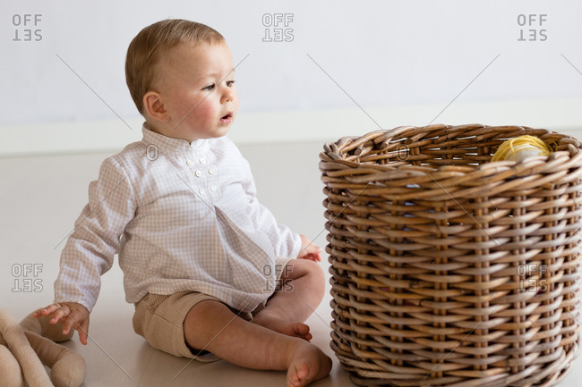 Curious little kid in casual wear sitting barefoot on floor at home and taking plush toys from wicker basket