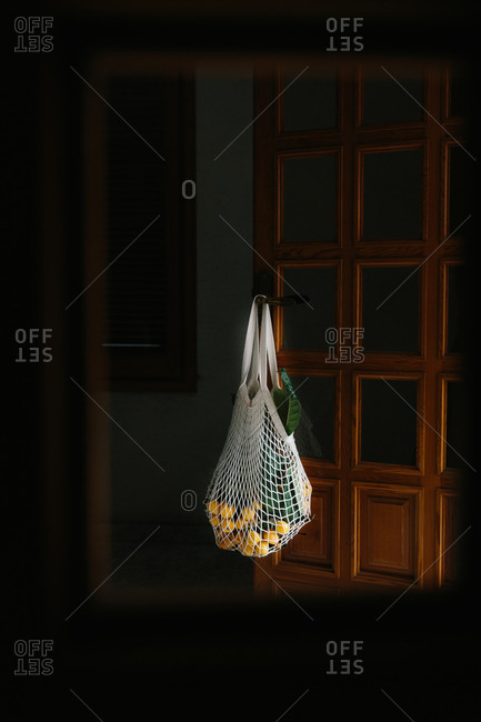 Reusable white string bag with fresh loquat fruits on branches hanging on knob of wooden door inside room with dark light