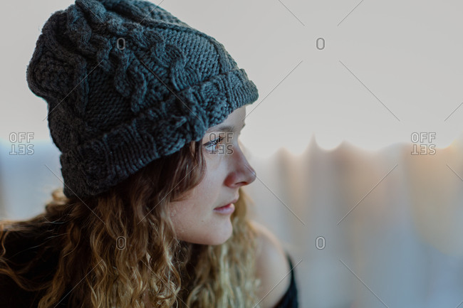 High angle of crop pensive millennial female in warm knitted hat looking away with melancholy and pondering against blurred interior of light room