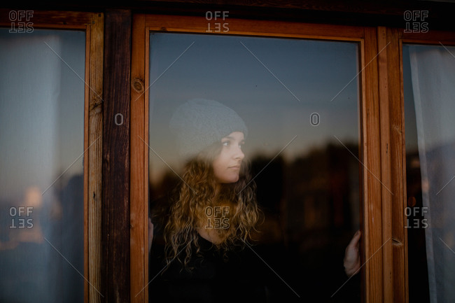 Through glass calm young female in casual warm sweater and knitted hat looking away and contemplating while standing beside window with reflection of countryside during amazing sunset