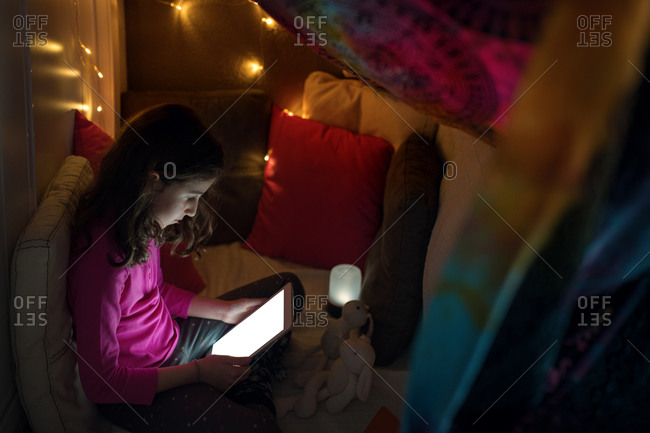 Calm little girl sitting inside cozy house made with cushions and blanket with glowing lamps and browsing tablet while spending time at home