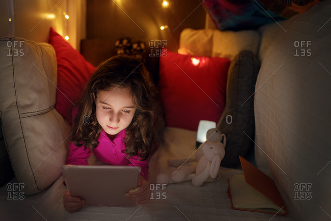 Calm little girl lying inside cozy house made with cushions and blanket with glowing lamps and browsing tablet while spending time at home