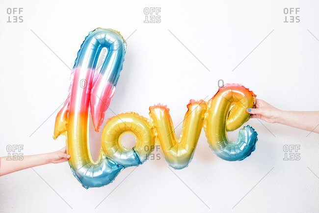 Colorful inflatable balloon in shape of word Love held by crop anonymous people against white background
