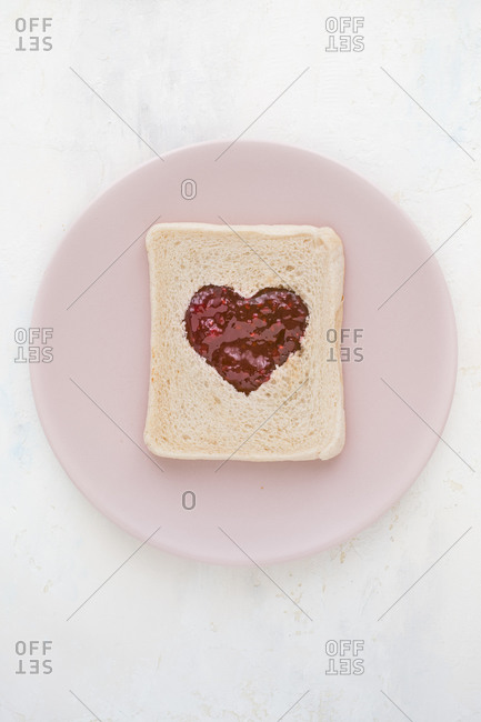 Top view of slice of white wheat bread garnished with sweet red berry jam in shape of heart served on pink plate