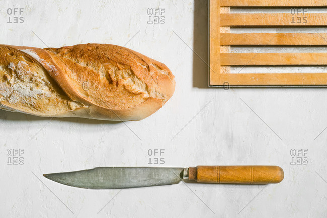 Top view composition with crispy artisan baguette placed on table with rustic knife and wooden board