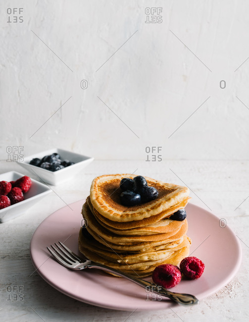 From above of stack of yummy homemade pancakes garnished with fresh berries served for breakfast on plate with fork on table
