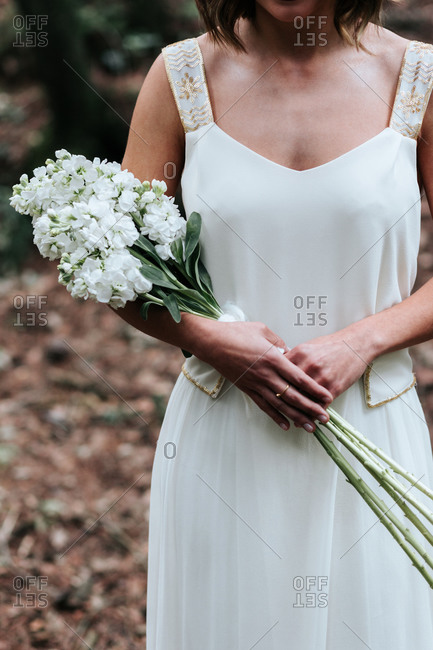 Crop young female in white dress and with bridal bouquet looking away while standing on narrow path near green trees in countryside