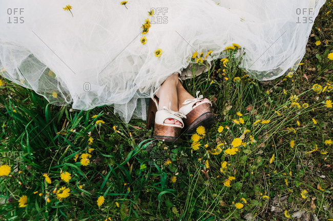 From above of newlywed female wearing white wedding dress and high heels sitting with crossed legs in blooming field with yellow flowers
