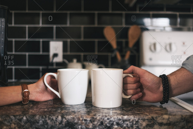 Crop anonymous partners in wristwatches taking big white mugs with drink while sitting at marble table during breakfast in kitchen near oven at home