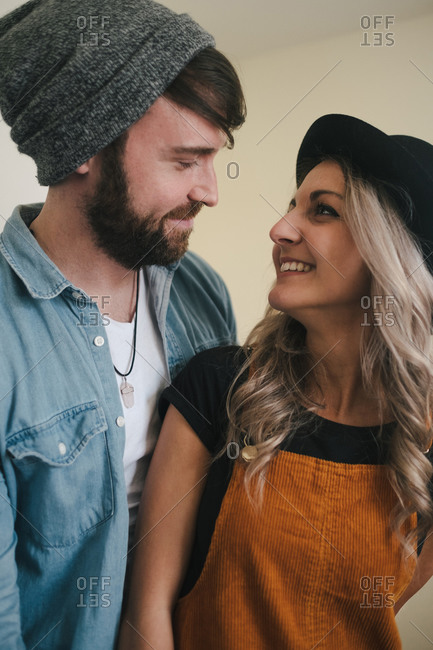 Cheerful woman in hat and smiling boyfriend in denim jacket cuddling while standing in kitchen looking at each other
