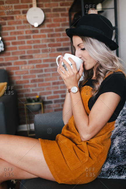 Side view of smiling young blond female drinking coffee while sitting on cozy chair in living room