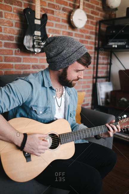 Side view happy bearded guitarist in sock cap and denim jacket playing acoustic guitar while sitting on couch with decorative pillow near brick wall with different musical instruments at home
