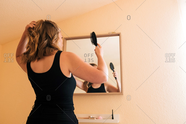 Low angle back view of young female in casual outfit brushing hair and making ponytail while standing in front of mirror at home