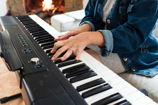 Crop female in casual wear sitting on sofa playing electric piano while spending time at home