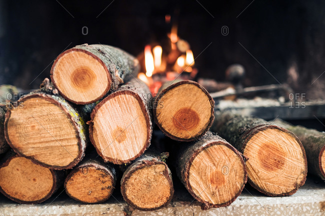 Closeup of fireplace with burning flame and firewood with smoke and ash