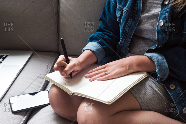 Crop young female in casual outfit taking notes in diary while sitting on sofa with gadgets in living room
