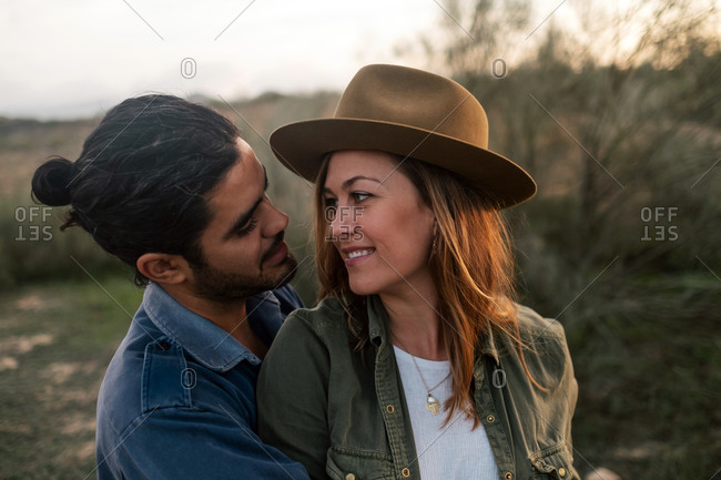 Cheerful man and woman embracing and looking at each other while standing near leafless bush during date in evening in nature