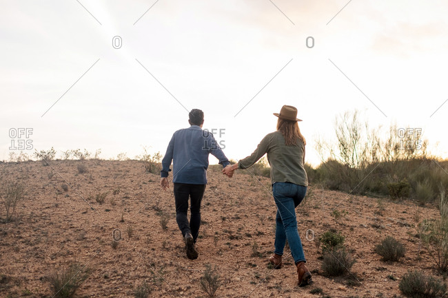 Cheerful man and woman standing in countryside