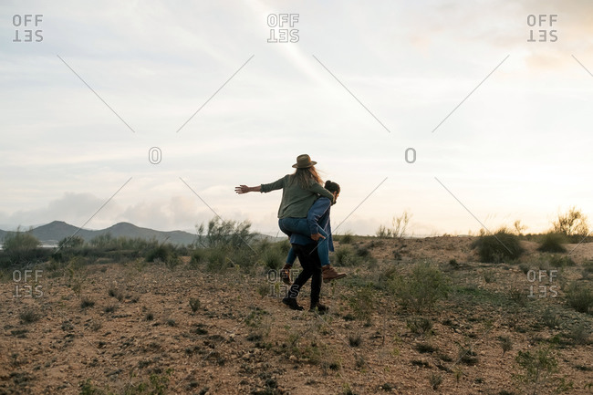 Full body man giving piggyback ride to happy girlfriend while standing in field against cloudy sundown sky in nature