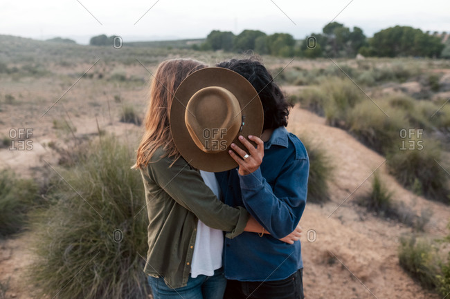 Unrecognizable man and woman hugging and hiding faces behind hat while resting on blurred background of field and sunset sky in nature