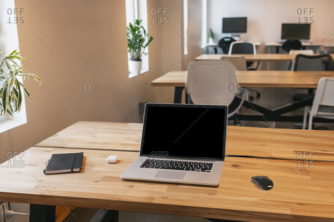 Netbook and mouse placed on wooden table with notebook and wireless earphones in creative workspace