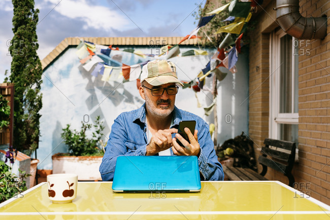 Thoughtful senior male in cap and browsing smartphone while sitting at laptop with mug of yummy hot drink in backyard of country house in sunny day