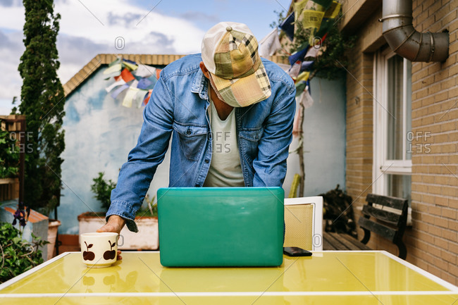 Thoughtful elderly male in cap and denim shirt focusing on screen with interest while sitting at table with mug of tasty beverage and using netbook in yard of country house