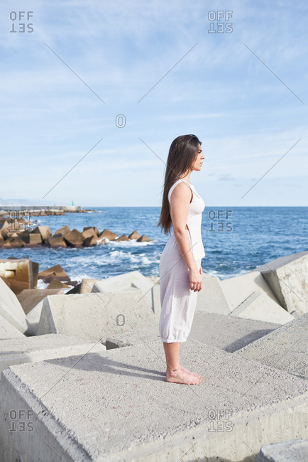 Side view full body young barefoot female in white clothes standing on concrete block of breakwater construction against sea and blue cloudy sky