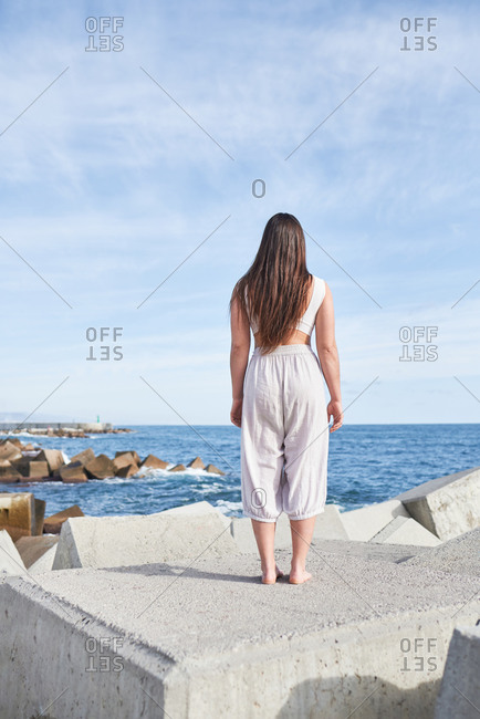 Back view full body of unrecognizable barefoot female in white clothes standing on concrete block of breakwater construction against sea and blue cloudy sky