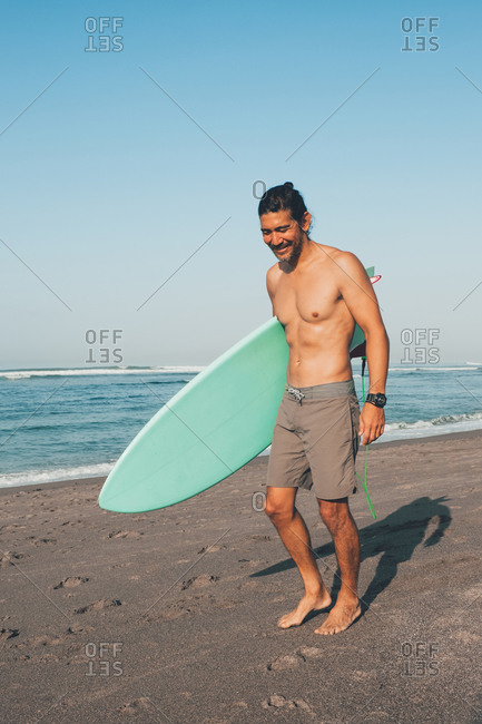 Happy shirtless ethnic male in shirts with blue surfboard looking away while standing on sandy beach near sea in sunny day