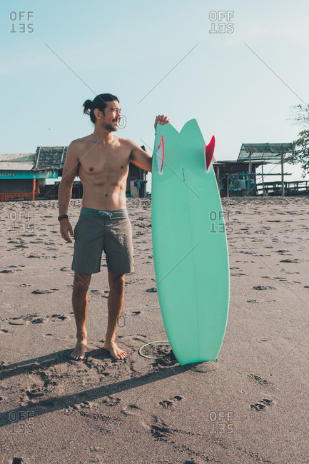 Happy shirtless ethnic male in shirts with blue surfboard looking away while standing on sandy beach near a seafront terrace coffee shop in sunny day