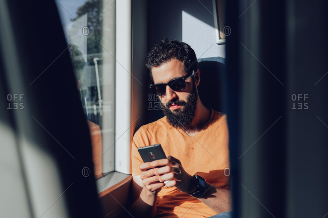 Calm bearded man in casual clothes and sunglasses using mobile phone while sitting on passenger seat near window in modern train