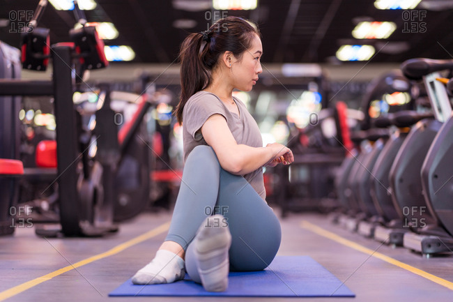 Focused young Asian sportswoman in sportswear sitting on mat and stretching looking away while training in modern fitness center