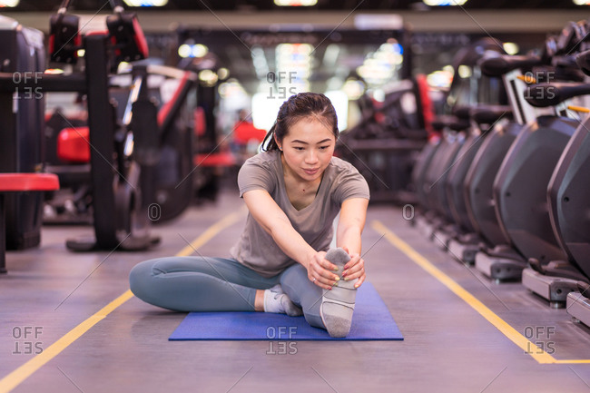 Focused young Asian sportswoman in sportswear sitting on mat and stretching leg while training in modern fitness center