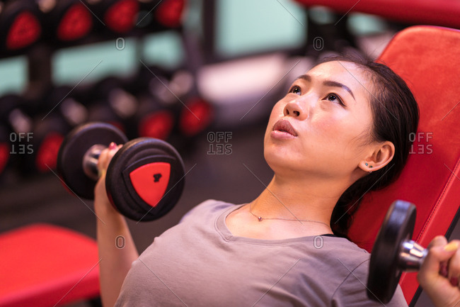 Powerful ethnic female athlete in sportswear doing dumbbells press on incline bench looking up in modern fitness center