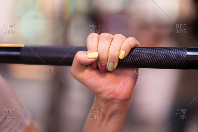 Cropped unrecognizable sportswoman hand with barbell in smith machine during intense workout in modern gym
