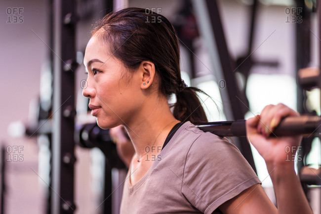 Side view of strong ethnic sportswoman in active wear squatting with barbell in smith machine during intense workout looking away in modern gym