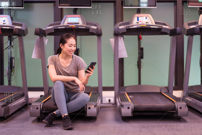 Positive young ethnic female athlete in active wear resting on treadmill and browsing smartphone while resting after workout in modern gym