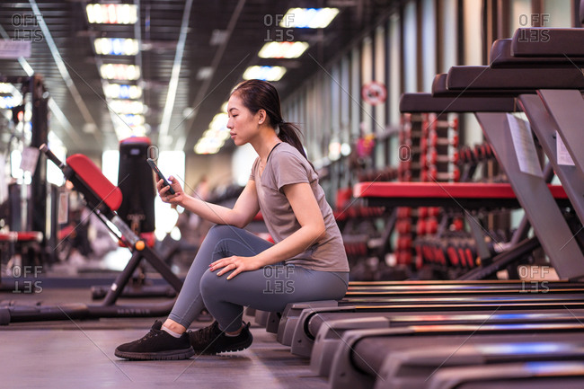 Side view of positive young ethnic female athlete in active wear resting on treadmill and browsing smartphone while resting after workout in modern gym