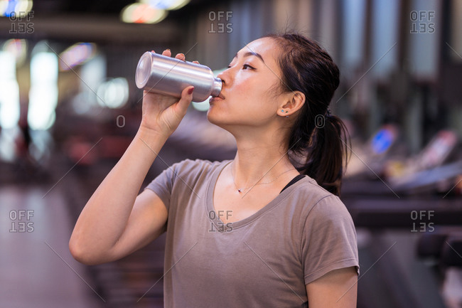 Slim young Asian sportswoman in sportswear drinking fresh water from bottle while resting after hard workout in modern gym