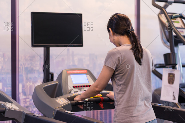 Back view of unrecognizable female athlete in sportswear running on treadmill during cardio workout in modern fitness center