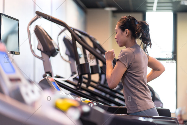 Side view of slim young ethnic sportswoman in active wear running on treadmill while exercising in spacious modern fitness center