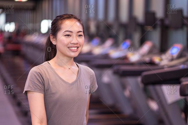 Slim happy young Asian sportswoman in sportswear walking in a gym after workout