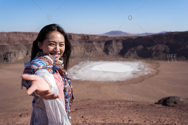 Happy Asian female traveler smiling while pointing at sodium phosphate crystal surface inside crater during trip in desert valley with rocky terrain