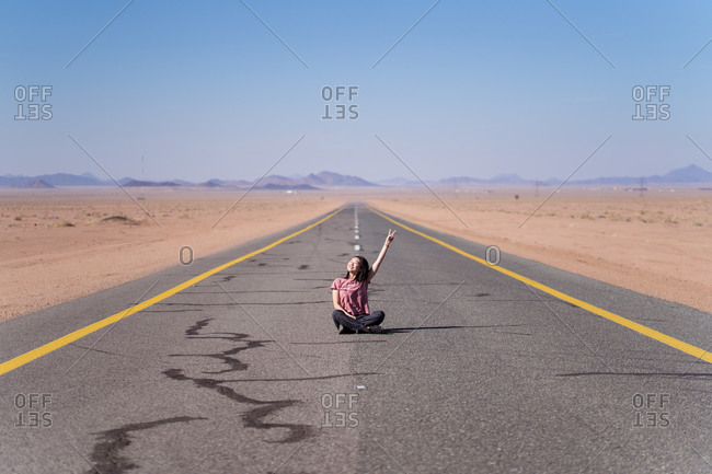 Smiling teen in casual wear sitting with crossed legs on asphalt road with yellow and white marking near sand and mountains behind and demonstrating peace gesture with raised hand