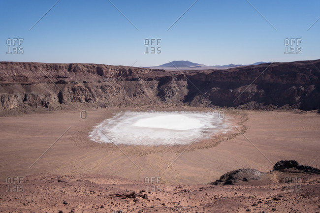 Aerial view of white sodium phosphate crystal surface placed inside maar crater at bright sunlight against blue clear sky and mountains