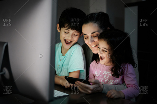 Happy young mother with little son and daughter holding smartphone while sitting together at table with computer and watching funny video in dark room at home