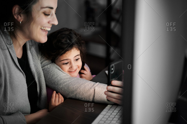 Cheerful young ethnic female with little daughter using mobile phone and communicating with friends via video chat while spending time at home